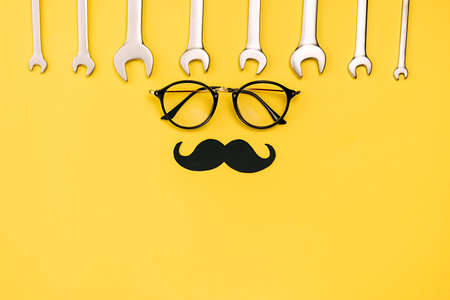 Holiday concept made with eyeglasses, stylish black paper photo booth props mustaches and combination wrenches on yellow background. Copy space for inscriptions. Creative idea.