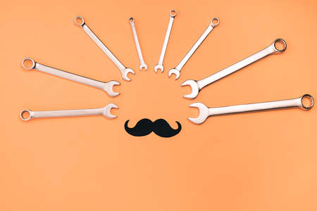 Fathers Day mockup with combination wrenches and retro stylish black paper photo booth props mustaches on orange background with copy space. Flat lay, top view, minimal composition Banque d'images