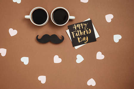 Two cup coffee, stylish black paper photo booth props mustaches, card with phrase happy father's day and many little hearts on brown background. Copy space for inscriptions. Holiday Concept. Stockfoto