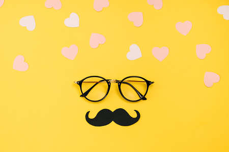 Creative holiday concept made with transparent glasses, stylish black paper photo booth props mustaches and many little hearts on yellow background. Copy space for inscriptions. Stockfoto