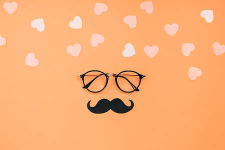 Eyeglasses, stylish black paper photo booth props mustaches and many little hearts on orange background. Copy space for inscriptions. Father's Day Holiday Concept.
