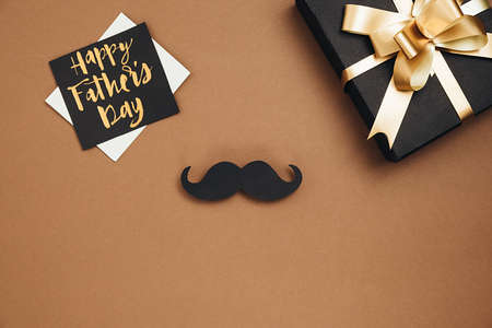 Happy fathers day concept. Top view of handmade gift box, card with phrase happy father's day and retro stylish black paper photo booth props mustaches on brown background. Flat lay, copy space Stockfoto