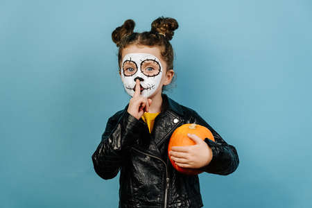 Face art and traditional Mexican holiday concept. Little girl child with orange pumpkin holding index finger at lips, asking to keep silence, dressed in Halloween costume, wears sugar skull makeup 免版税图像