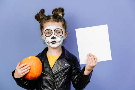 Cute little girl wears frightening makeup, hold orange pumpkin and white blank for advertisement, isolated on purple studio background, dressed in black leather jacket. Happy Halloween!
