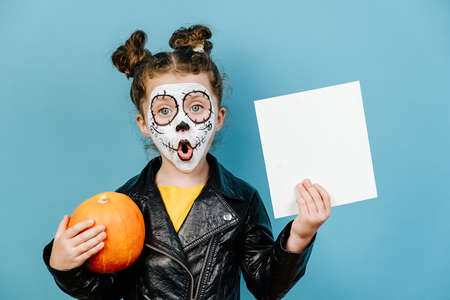 Shocked little girl wears frightening makeup, hold pumpkin and white blank for advertisement, dressed in black leather jacket, isolated on blue studio background. Happy Halloween! Imagens
