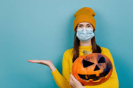 Young woman in medical mask, hold spooky pumpkin, showing empty copy space on open hand palm, wears orange sweater and hat, poses over on blue background. Halloween and coronavirus pandemic concept