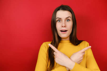 Questioned uncertain young woman crossed arms over chest, gives two variants and advertises product, wears sweater, asks advice as cant pick something, makes decision confusing. Concept options Stock Photo