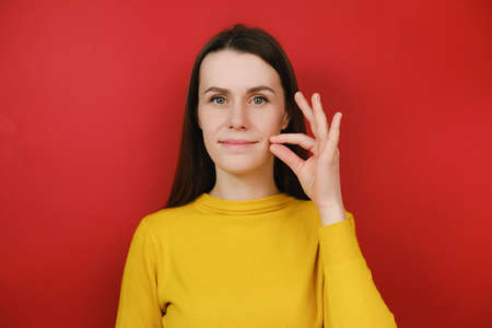 Sly smiling young woman looks mysteriously, aside zips her mouth shut, promises to keep secret, holds fingers near cheek, hides information, dressed in yellow sweater, isolated on red background
