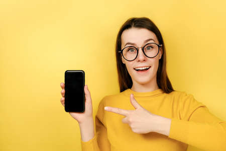 Happy young woman in spectacles, points at smart phone device, shows blank screen for your promotional content, wears sweater, advertizes new device for customers, isolated over yellow background