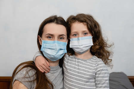 Close up little cute girl wearing medical face mask hugging mom, give support, looking at camera, sitting on bed at home. Concept of coronavirus or COVID-19 pandemic disease symptoms. Home quarantine.