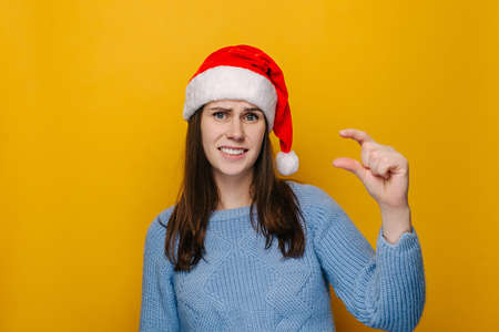 Young female shows very tiny object, shapes something small, wears Christmas hat and blue sweater, female looks in puzzlement, need some more, isolated over yellow studio wall. New Year concept