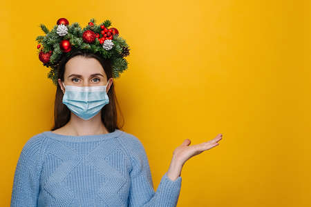 Horizontal shot of young woman in medical face mask holds invisible object, keeps palm raised, demonstrates something over yellow background, wears winter sweater, handmade wreath. Covid-19 concept