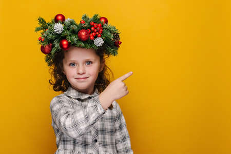 Happy cute little kid girl points with fore finger at free space for advertising content, wears spruce holiday wreath around head, isolated on yellow wall. New Year celebration merry holiday concept