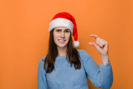 Upset young woman shapes little gesture, demonstrates something very tiny, wears blue sweater and xmas red hat, measures small size, isolated over orange background with copy space. Not very much