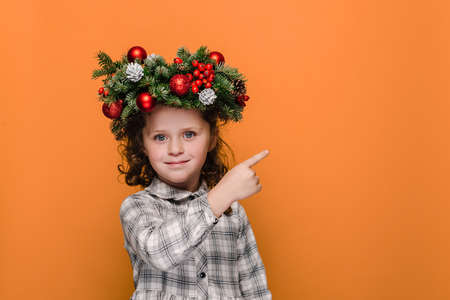 Happy little kid girl points with forefinger at free space for advertising content, wears spruce holiday wreath around head, isolated on orange studio background. New Year and Christmas concept