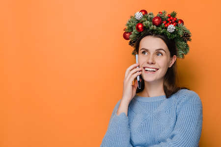 Beautiful smiling woman wears Christmas wreath, talking on mobile phone conducting pleasant conversation, isolated on orange studio wall with copy space for your advertising content. Happy New Year