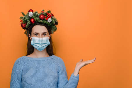 Portrait of young brunette woman in medical face mask holds invisible object, keeps palm raised, demonstrates something over orange background, wears blue sweater, handmade wreath. Covid-19 concept