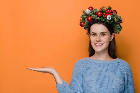 Cheerful woman with charming smile keeps palm raised against orange copy space, looks aside, wears Christmas wreath and cozy sweater, demonstrates something. Happy New Year celebration merry holiday 免版税图像
