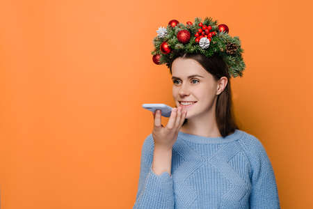 Translator app concept. Cute young woman holds phone talks on speakerphone with friend, makes voice recognition or request uses internet services through virtual assistant, wears Christmas wreath.
