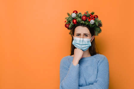 Grumpy displeased female in medical face mask, keeps hands half crossed, holds chin, has angry expression, being deep in thoughts, dressed in winter sweater, models over orange studio background 免版税图像