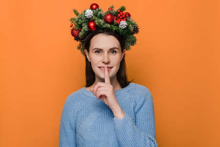 Positive female in handmade wreath, has toothy smile, makes hush gesture, wears winter sweater, poses against orange wall with copy space for advertisement. New Year celebration merry holiday concept 免版税图像