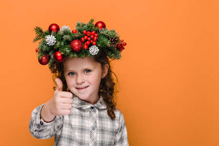 Close up portrait of cute little kid girl showing thumbs up like gesture, wears spruce holiday wreath around head, isolated over orange background studio with copy space. Nappy new year concept