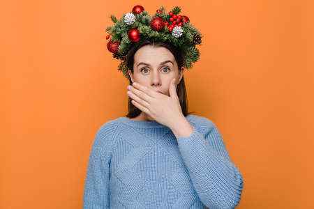 Excited female covers mouth with happiness, doesn't expect to receive pleasant surprise, being thankful and pleasantly shocked, isolated over orange wall. Happy New Year celebration merry holiday