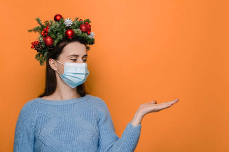 Young Caucasian woman in medical face mask, keeps hand raised, dressed in winter sweater and handmade wreath, pretends holding something, isolated over orange background. Xmas and Covid-19 concept
