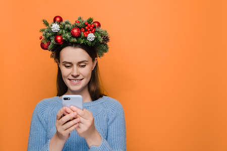 Cheerful young woman types text message on cell phone, enjoys online communication, types feedback, wears handmade Christmas wreath and winter sweater, models over orange background. Xmas concept