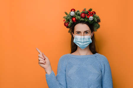 Horizontal shot of young woman wearing medical mask points with hand aside, shows copy space for advertisement, wears spruce holiday wreath, isolated on orange wall. Covid-19 and New Year concept