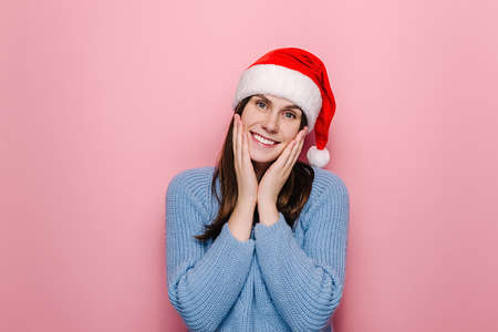 Happy European woman keeps hands on cheeks, wears Christmas red hat and cozy blue sweater, poses against pink studio background. Cheerful lovely feminine girl feels amused. Xmas and new year concept