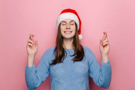 Cheerful young woman stands with fingers crossed, awaits miracle happen, wears Christmas hat and cozy sweater, believes in good luck, isolated over pink background. Making Christmas wish concept