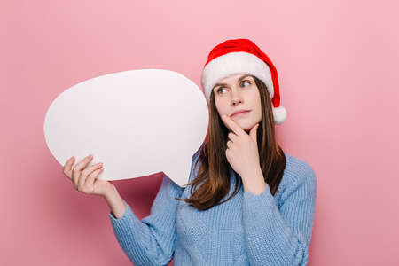 Dreamful young woman holding empty speech bubble stands with fingers crossed, awaits miracle happen, wears Christmas hat and sweater, believes in good luck, isolated on pink background. Wish concept