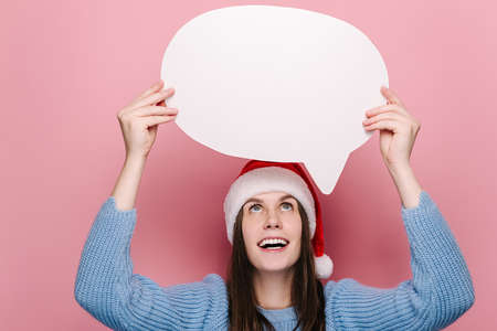 Portrait of cheerful young woman holding speech bubble, dressed in cozy blue sweater and Christmas red hat, isolated on pink studio background. Happy New Year celebration merry holiday concept