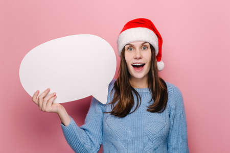 Happy shocked young woman holding blank speech bubble, dressed in Christmas red hat and cozy blue sweater, models over pink studio background with copy space for advertisement. New Year concept