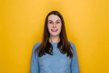 Overjoyed glad young woman with happy face keeps mouth wide opened laughs at something joyfully doesn't hide emotions grins from happiness, wears blue sweater, isolated on yellow studio background.