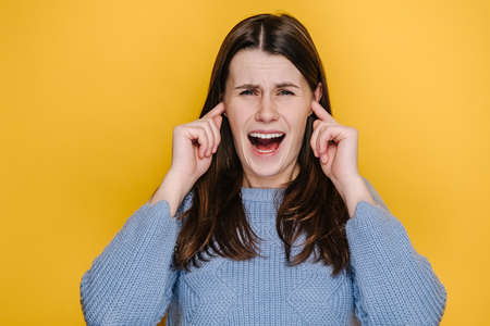 Portrait of crazy frustrated young caucasian woman cover ears with fingers keeping screaming, dressed in blue sweater, posing isolated on yellow studio background. Emotion people lifestyle concept