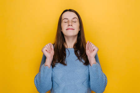 Young woman raises hands stands with closed eyes smiles pleasantly has big desire something good happen, wears blue knitted sweater, isolated on yellow wall, awaits miracle or moment dream come true