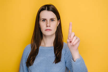 Portrait of young brunette woman warning with admonishing finger gesture, saying no, giving advice to avoid danger, dressed in blue sweater, disapproval sign, isolated on yellow studio background 免版税图像