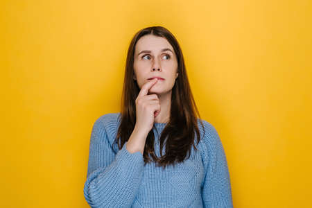 Portrait of attractive young woman keeps finger on lips looks with pensive expression above makes important decision builds plans in mind, wears blue sweater, isolated on yellow studio background