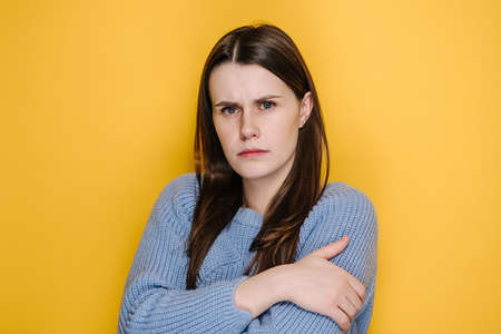 Depressed lonely unhappy young woman looking at camera with gloomy sad expression, millennial girl feeling insulted or offended, wears sweater, isolated on yellow studio background with copy space