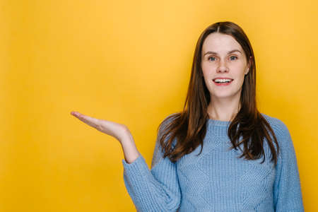 Smiling cute young woman looks pleasant to her palm hand, showing something in her hand, wears blue sweater, isolated on yellow studio background with copy space. People sincere emotions concept