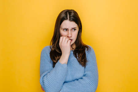 Worried young woman folded hands together near mouth, gnawing nails, female feels uncertain, stressed. Confused brunette girl with frighten or panic gesture, isolated on yellow studio background