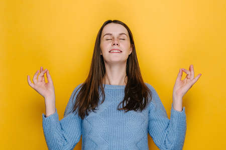 Attractive cute young woman hold hands in yoga gesture relaxing meditating trying to calm down blinking, dressed in knitted blue sweater, isolated on yellow studio background. People lifestyle concept