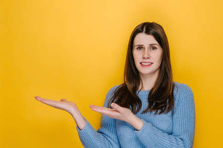 Displeased young woman looking camera pointing showing fingers hands on workspace copy space mock up template. Sad girl in blue sweater, isolated on yellow studio background. People lifestyle concept 免版税图像