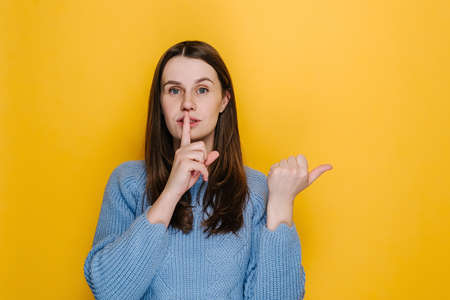 Young caucasian female point with finger at blank copy space aside, girl make hush be quiet gesture, tell about show secret sale offer, dressed in blue sweater, isolated on yellow studio background 免版税图像