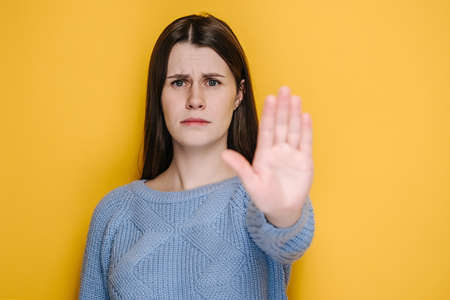 Confident serious millennial young female showing stop gesture, displeased brunette girl look at camera refuse from inept suggestion or offer, wears blue sweater, isolated on yellow studio background