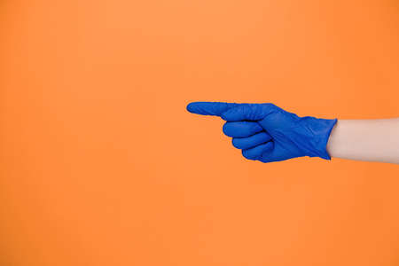 Close up of male finger pointing at copy space, wears medical protective latex gloves, isolated on orange studio background with copy space for advertisement. Advertising area, mockup. Hand gesture 免版税图像