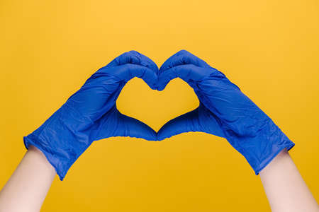 Close up of male hands in medical protection blue gloves making heart symbol as a way to show thank gratitude to doctors and nurses for help in fight against disease, isolated on yellow wall.