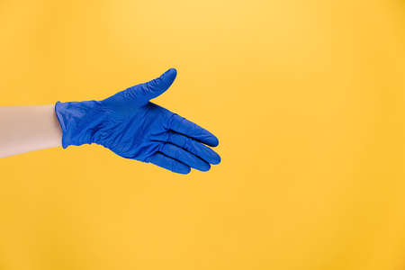 Welcome gesture. Open palm. Close up of unrecognizable male hand in protective blue gloves, isolated on yellow background with copy space for advertisement. Advertising background. Covid-19 concept